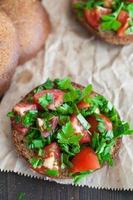 bruschetta al pomodoro italiano con verdure tritate, erbe e olio foto