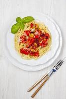 spaghetti di pasta con peperoni e basilico fresco un bianco foto