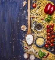 concetto di pasta di cottura pomodori, formaggio, pepe, spezie, aglio, cucchiaio, bordo, foto