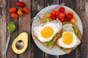avocado sano, toast di uova con pomodori su fondo di legno rustico foto