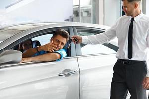 consulente di vendita che mostra la nuova auto a un potenziale acquirente foto
