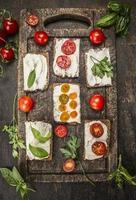 fondo di legno rustico del tagliere delle erbe fresche dei pomodori del formaggio dei panini foto