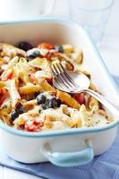 penne al forno con pomodorini, olive e salsa di formaggio foto