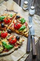 pizza fresca su carta e vecchia tavola di legno