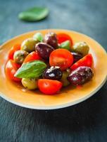 olive verdi nere marinate con insalata di foglie di basilico di pomodorini. foto