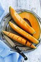 fette di melone cantalupo su piastra rustica in metallo.