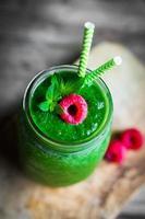 Frullato verde fresco su fondo di legno rustico foto