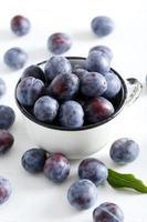 prugne fresche in tazza su fondo di legno bianco foto