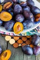 prugne fresche succose su una tavola di legno foto