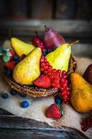 Pere con frutti di bosco su fondo in legno