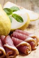 pera e prosciutto italiano su una tavola, fuoco selettivo foto
