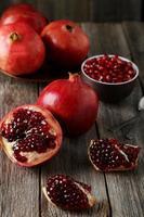 delizioso frutto di melograno su fondo di legno grigio foto