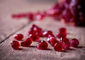semi di melograno rosso sul vecchio tavolo di legno foto