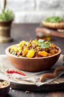 lenticchie con ragù di carote e zucca in una ciotola di legno. foto
