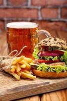 hamburger alla griglia con patatine fritte e birra su sfondo di muro di mattoni