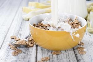 versando il latte in una ciotola con cornflakes foto