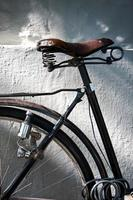 dettaglio di un seggiolino da bicicletta vintage, ruota, dinamo e lucchetto foto