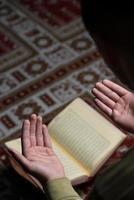 giovane ragazzo musulmano che legge il Corano foto