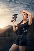 donna potente che tiene la pistola in stile film d'azione foto