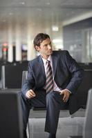 uomo d'affari seduto in aeroporto.