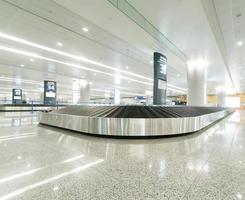 valigia singola da sola sulla giostra dell'aeroporto foto