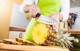 mani della donna che tagliano ananas