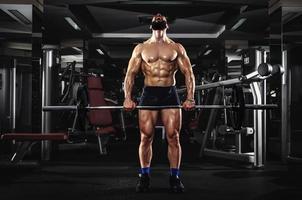 uomo muscoloso sollevando alcuni pesanti bilancieri foto