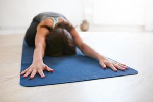 donna che si distende nella posa del bambino che fa yoga foto