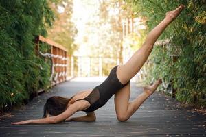 la giovane donna sta praticando yoga foto