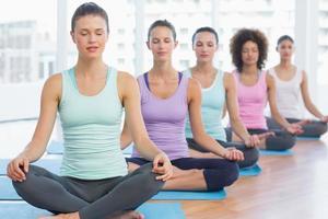 le donne sportive in meditazione posano con gli occhi chiusi foto