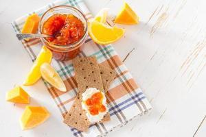 marmellata in barattolo di vetro con ingredienti e pane croccante foto