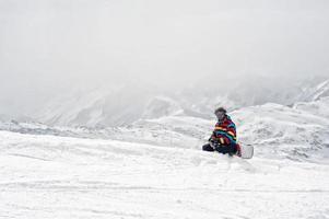 lo snowboarder si siede in cima alla montagna foto