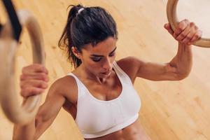 donna forte facendo pull-up utilizzando anelli di ginnastica in palestra foto