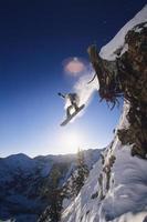 lo snowboarder che salta dalla sporgenza della montagna foto