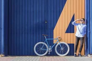 uomo d'affari in piedi accanto alla sua bicicletta foto
