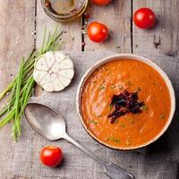 zuppa di pomodoro con pomodori secchi. fondo in legno foto