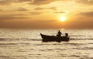 barca da pesca sagoma in mare al tramonto sullo sfondo. foto