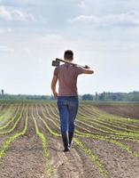 contadino con zappa in campo di mais foto