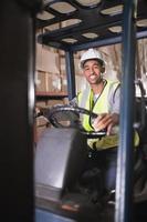 autista che aziona la macchina del carrello elevatore in magazzino foto