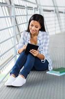 studente universitario femminile utilizzando il computer tablet foto