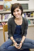 studentessa che utilizza telefono cellulare nella biblioteca foto