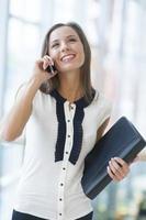 donna di affari sulla cartella e sul sorridere della tenuta del telefono cellulare foto