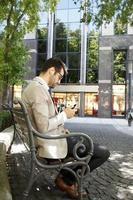 uomo d'affari seduto nel parco