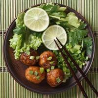polpette di pesce con lime ed erbe sul tavolo di bambù foto