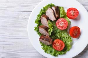 carne di anatra fritta con il primo piano di pomodori dall'alto. orizzontale foto