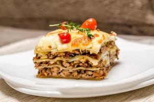 porzione di lasagne sul piatto quadrato foto