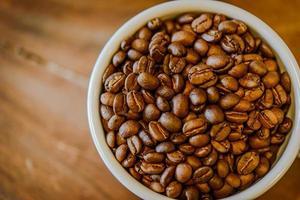 chicchi di caffè in tazza su sfondo di legno grunge
