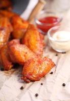 ali di pollo con salsa su carta marrone foto