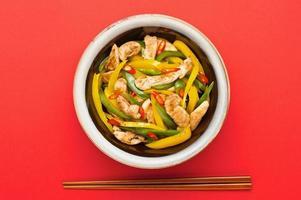pollo fritto con peperone sul tavolo rosso foto