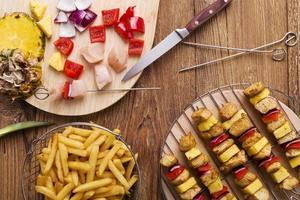 servire spiedini di pollo alla griglia con ananas, peperoni e cipolle
